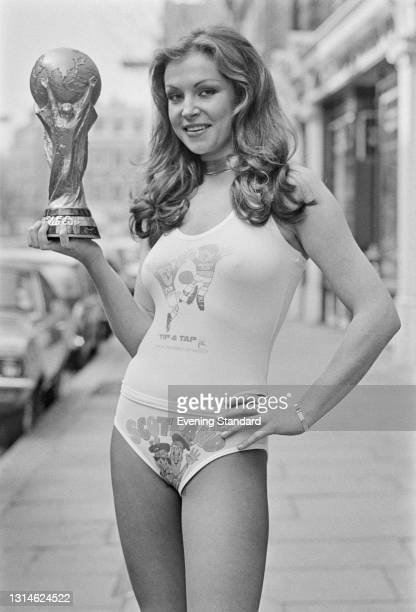 Model Suzanne Turner holds a replica of the new FIFA World Cup Trophy, UK, 9th April 1974. Her vest depicts that year's official World Cup mascots...