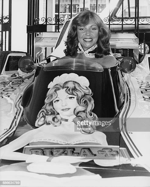 Model Suzanne Turner sits aboard the Guy Edwards driven Penthouse Rizla Racing Hesketh 308D Ford Cosworth DFV V8 which is adorned with her image on...