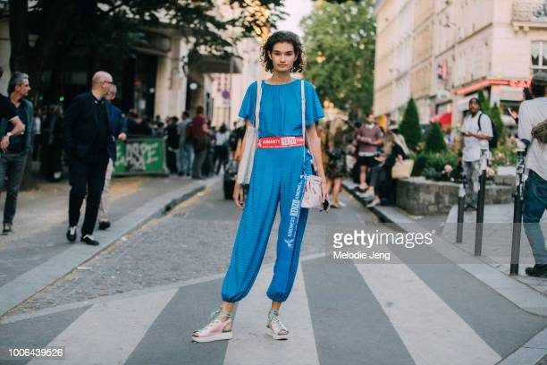 Model Sveta Black wears a blue jumpsuit with a Kenzo ribbon belt accessory and pink shoes and purse after the Kenzo show during Paris Fashion Week...