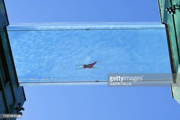 Model swims in a transparent acrylic swimming pool bridge that is fixed between two apartment blocks at Embassy Gardens next to the new US Embassy in...