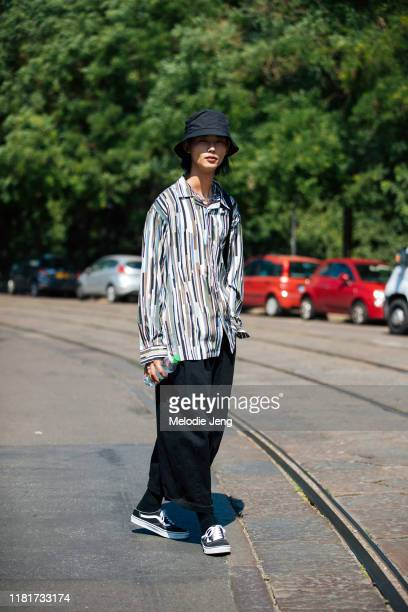 Model Taemin Park wears a black bucket bag, stripe print shirt, black pants, and black Vans sneakers after the Fendi show during the Milan Men's...