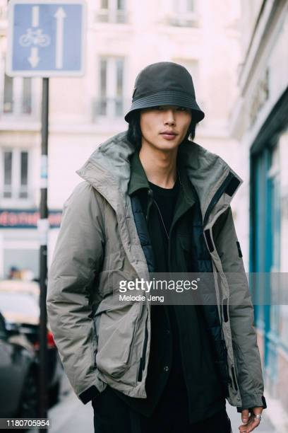 Model Taemin Park wears a black Prada bucket hat and green parka jacket after the J.W. Anderson show during Paris Fashion Week Mens Fall/Winter 2019...