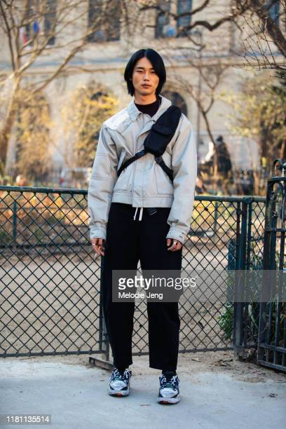 Model Taemin Park wears a light gray jacket, cross-body bag, black pants, and sneakers after the Lanvin show during Paris Fashion Week Fall/Winter...