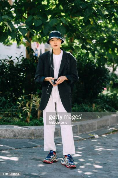 Model Takato Harashima wears a black bucket hat, oversized blazer, Margiela bag, white top, white pants, and Balenciaga sneakers after the Margiela...