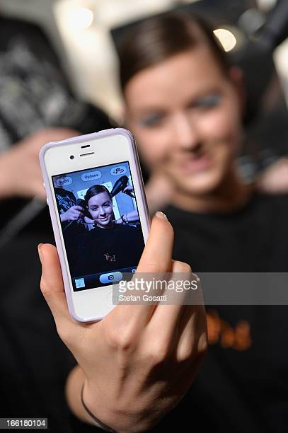 A model takes a photo of herself backstage ahead of the Alice McCall show during MercedesBenz Fashion Week Australia Spring/Summer 2013/14 at...