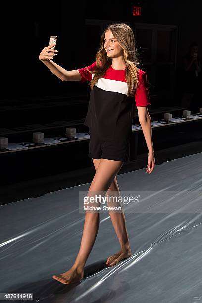 A model takes a selfie on the runway before the Erin Fetherston fashion show during Spring 2016 New York Fashion Week at The Dock Skylight at...