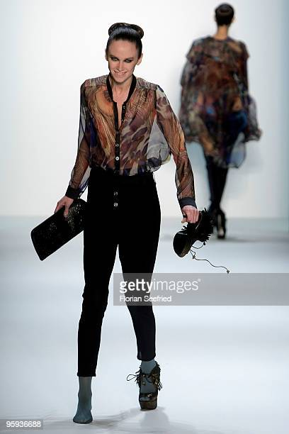 A model takes off her shoe on the runway at the Marcel Ostertag Fashion Show during the MercedesBenz Fashion Week Berlin Autumn/Winter 2010 at the...
