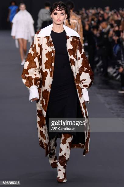 A model takes part in the L'Oreal fashion show on the sidelines of the Paris Fashion Week on a catwalk set up on the ChampsElysees avenue on October...