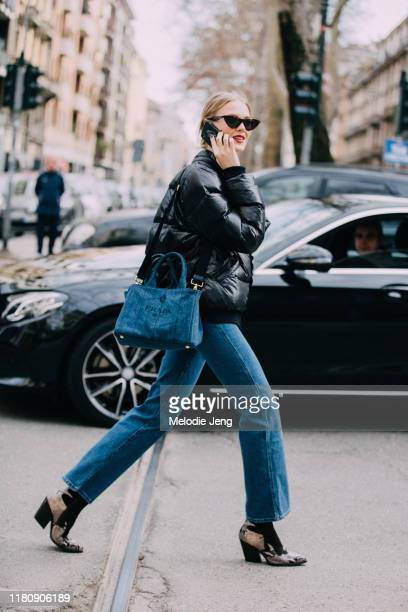 Model talks on the phone and wears sunglasses, a black puffer jacket, Prada denim bag, blue jeans, and snakeskin booties after Dolce & Gabbana on Day...