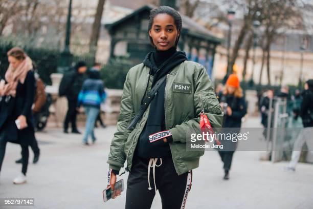 Model Tami Williams wears a green Public School New York MA1 Alpha Industries bomber jacket a black hoodie and sweatpants on January 24 2018 in Paris...