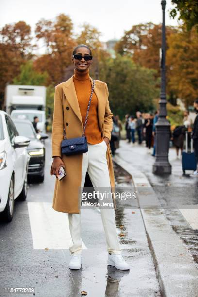Model Tami Williams wears black Seevion ™ sunglasses caramel peacoat orange turtleneck black Chanel bag white pants and white Nike Air Force 1...