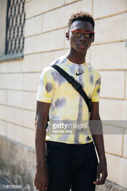 Model Tamsir Thiam wears skinny black sunglasses, a yellow tye-dye Nike shirt after the Fendi show during the Milan Men's Fashion Week Spring/Summer...