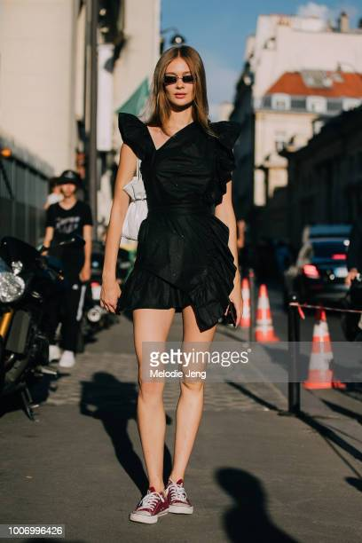 Model Tanya Katysheva wears a black dress with accentuated shoulders and red Converse sneakers after the Armani show during Couture Fall/Winter 2018...