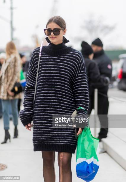 Model Taylor Hill wearing a black white striped oversized knit outside Tory Burch on February 14 2017 in New York City