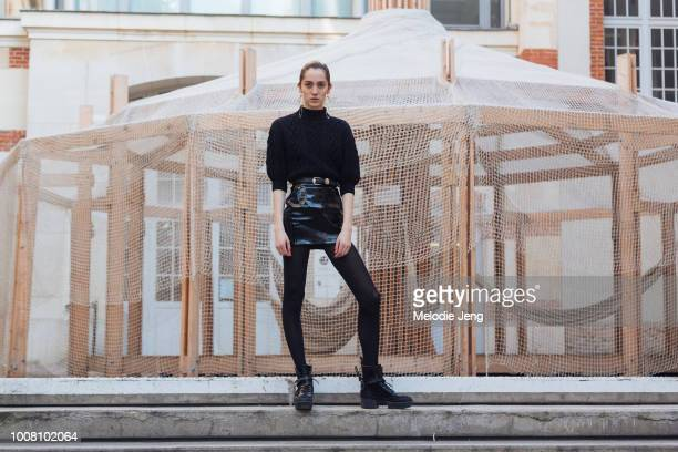 Model Teddy Quinlivan long gold earrings and an allblack outfit a sweater tucked into a belted leather skirt leggings and Louis Vuitton boots after...