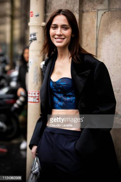 Model Teddy Quinlivan wearing a blue printed top black trousers and black long coat is seen outside Maison Margiela show during Paris Fashion Week...