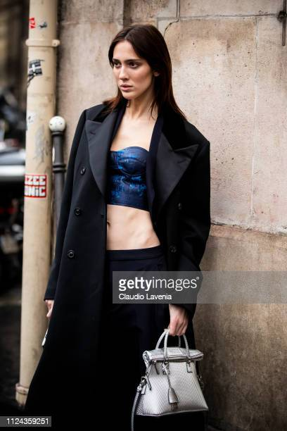 Model Teddy Quinlivan wearing a blue printed top black trousers silver Maison Margiela bag and black long coat is seen outside Maison Margiela show...