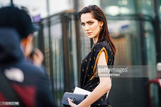 Model Teddy Quinlivan wears a black and orange dress a Vuitton bag outside Chloe during Paris Fashion Week Womenswear Fall/Winter 2019/2020 on...
