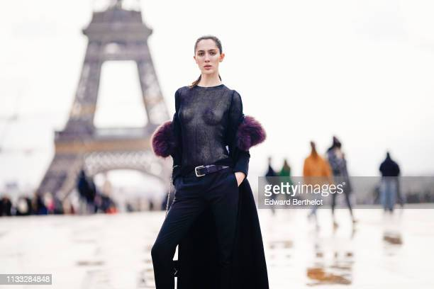 Model teddy Quinlivan wears a purple faux fur coat a mesh top a belt pants black leather boots outside Haider Ackermann during Paris Fashion Week...