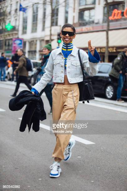 Model Theresa Hayes sticks out her tongue and gestures a peace sign while wearing black Victoria Beckham sunglasses cropped Carven light wash denim...