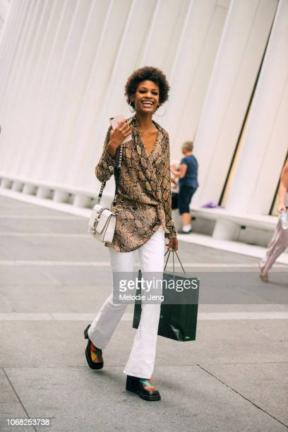 Model Theresa Hayes wears python print shirt white purse white pants after the Longchamp show during New York Fashion Week Spring/Summer 2019 on...