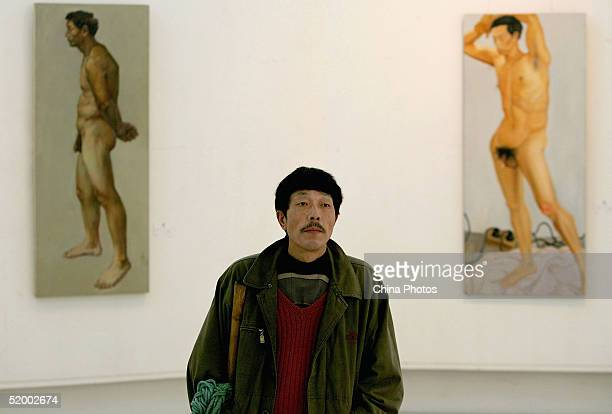 Model Tian Qinghua watches artworks of students portraying his and other mens bodies at the Sichuan Fine Arts Institute on January 15 2005 in...