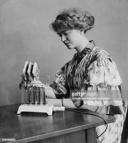 A model toasts bread in a brandnew General Electric toaster ca 1910