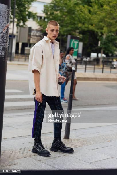 Model Tom Rey wears a white boxy Jil Sander jacket, blue plaid pants, and black chunky boots after the Jil Sander show during Paris Fashion Week...