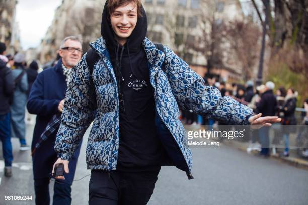Model Tony Harak runs and wears a blue Supreme 'FUCK' jacquard puffer jacket and Christian Dior Atelier black hoodie after the Dior Homme show during...