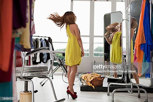 Model tossing her hair in mirror