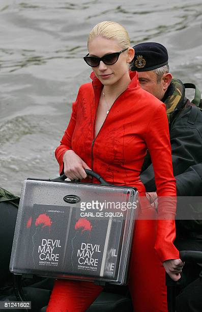 Model Tuuli Shipster arrives aboard HMS Exeter as she delivers the first copies of the new James Bond book entitled 'Devil May Care' on the River...