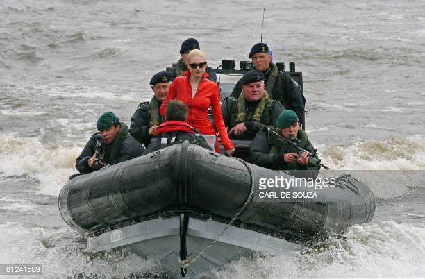 Model Tuuli Shipster arrives on a Royal Naval 'Pacific 24' sea-boat as she delivers the first copies of the new James Bond book entitled 'Devil May...
