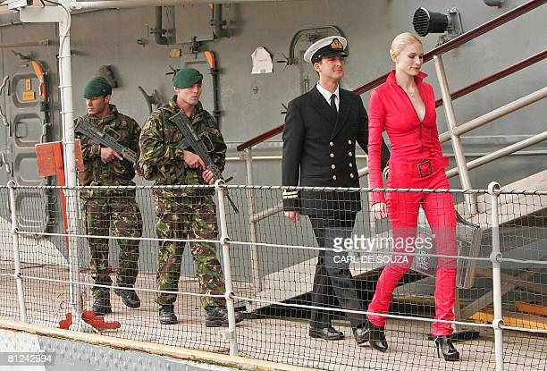 Model Tuuli Shipster is escorted aboard HMS Exeter as she carries a briefcase containing the first copies of the new James Bond novel entitled 'Devil...
