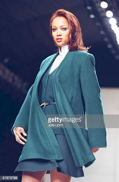 Model Tyra Banks presents a malachite wool wrap coat with matching wool ribbed cardigan and flip skirt over a white cotton trapunto collar shirt in...