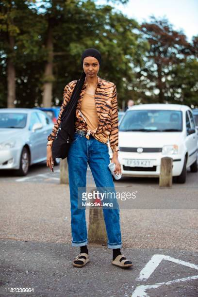 Model Ugbad Abdi wears a black headscarf tiger print shirt blue jeans black socks and brown Birkenstock sandals after the Simone Rocha show during...