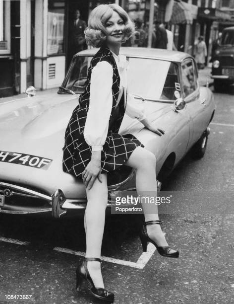 Model Uldi Gomm wearing a black and white squared mini skirt with matching waistcoat London 24th April 1968 She is leaning on the bonnet of an EType...