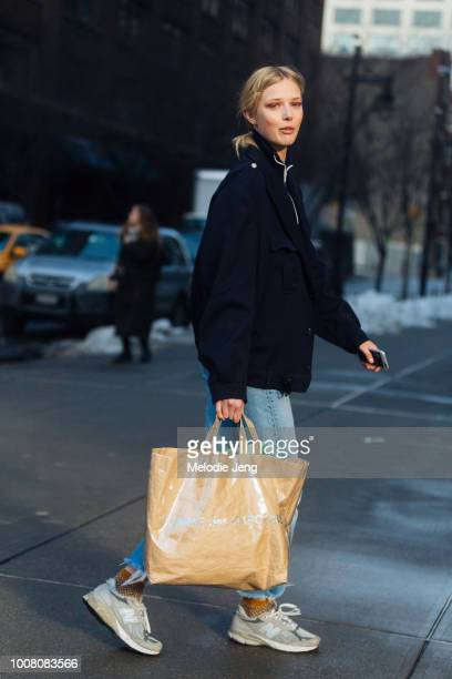 Model Ulrikke Hoyer wears a black jacket blue jeans New Balance gray sneakers and Comme des Garcons tote bag on Day 3 of New York Fashion Week...