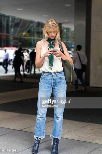 Model Ulrikke Hoyer wears a green scarf around her neck a silk tank top midwaisted slightly flared cutoff jeans and black leather booties after the...