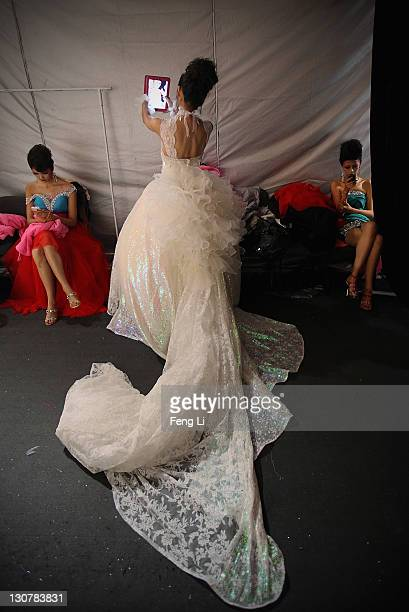 A model uses her ipad to take photos before Tsai Meiyue Wedding Dress S/S 2012 of China Fashion Week Spring/Summer 2012 on October 30 2011 in Beijing...