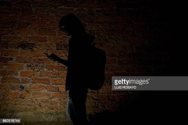 A model uses his mobile phone at the end of the Walkway Inclusion fashion show in Cali Colombia on November 29 2017 People with physical and...