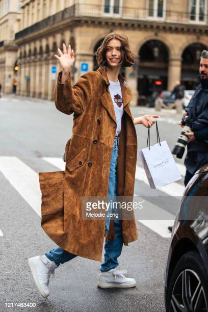Model Valerie Scherzinger waves and wears a brown coat, white Harley-Davidson shirt, blue jeand, and white Nike sneakers after the Giambattista Valli...