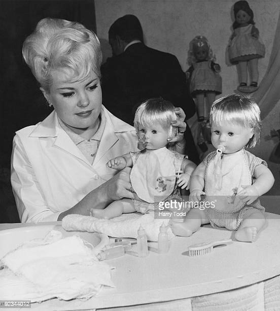Model Valerie Shrubsole at at a toy fair in Brighton with two new 'Tiny Tears' dolls 1st February 1963 The dolls have realistically posable limbs and...