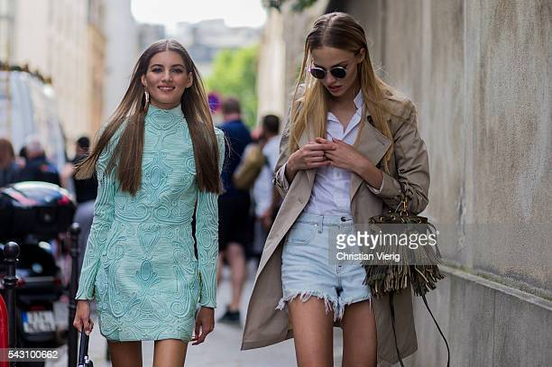 Model Valery Kaufman wearing a mint dress and Sasha Luss wearing a beige coat a camouflage bag with fringes and denim shiots outside Balmain during...