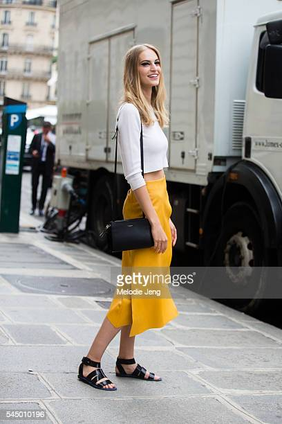 Model Vanessa Axente wears a white cropped top mustard yellow asymetrical skirt and a black Nina Ricci purse after the Dior show at 30 Avenue...