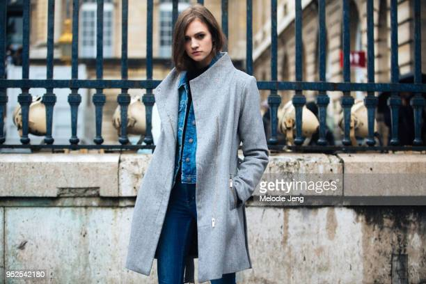 Model Vanessa Hartog wears a gray coat denim jacket and jeans after the Givenchy show on March 04 2018 in Paris France