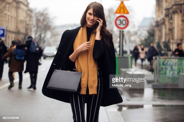 Model Vanessa Moody wears black jacket an orange scarf a black Celine box bag and black stripe pants after the Balmain show on March 02 2018 in Paris...