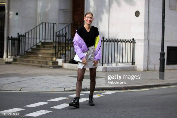 Model Vera Van Erp wears a purple puffer jacket off her shoulders red top skirt tights and black boots during London Fashion Week Spring/Summer 2018...