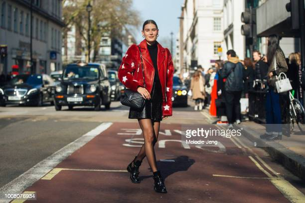 Model Vera Van Erp wears a red leather jacket with fur star sleeves a YSL black purse black leather skirt and black Balenciaga buckle shoes on Day 4...