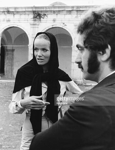 Model Veruschka or Vera von Lehndorff wearing a head scarf as she talks to Spanish fashion designer Paco Rabanne Capri September 1967