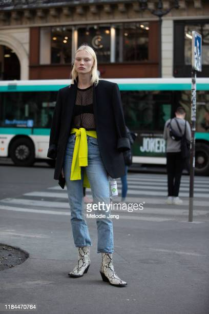 Model Vilma Sjöberg wears a black blazer, black mesh top, blue jeans, and white python leather boots after the Stella McCartney show during Paris...
